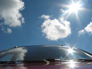 Cumulous Clouds and sun reflecting off car window
